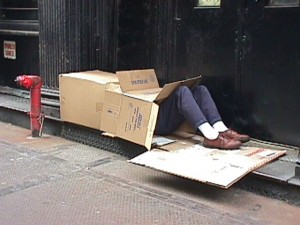 homeless man on the street in a cardboard box