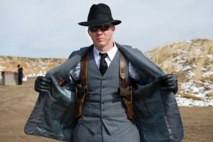 well dressed man with dual shoulder holsters carrying 1911 handguns